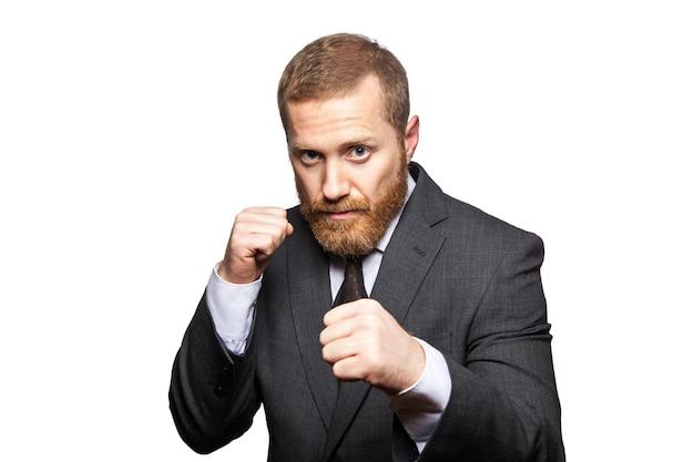 Pewny siebie biznesmen gotowy do walki i boksu. patrząc na strzał studio aparatu, na białym tle.