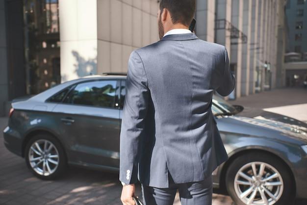 Pewny siebie biznesmen młody biznesmen przychodzi do samochodu
