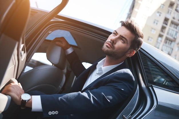 Pewny siebie biznesmen modny mężczyzna wychodzący z samochodu