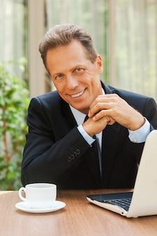 Pewny siebie biznesmen. pewny siebie dojrzały mężczyzna w stroju formalnym uśmiechający się i patrzący w kamerę siedzący przy stole z laptopem