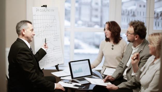 Pewny siebie biznesmen pokazując partnerom biznesowym nowy projekt komercyjny. koncepcja partnerstwa