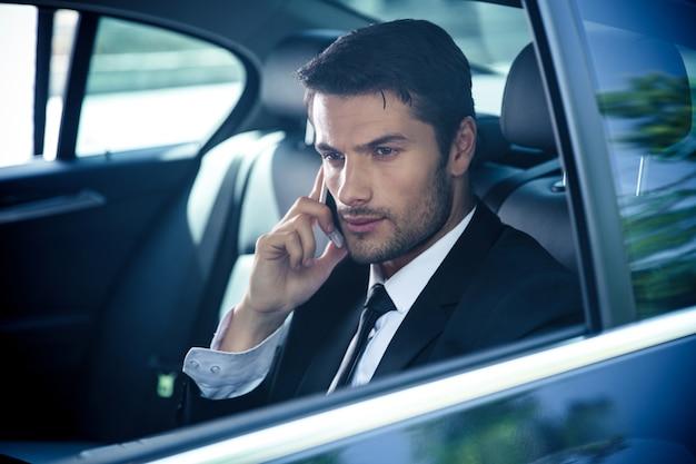 Pewny siebie biznesmen rozmawia przez telefon w samochodzie