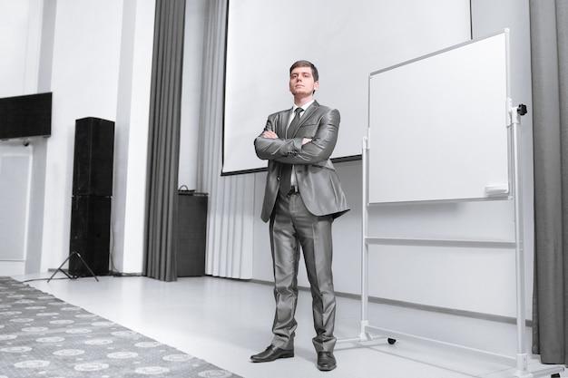 Pewny siebie biznesmen stojący na scenie w sali konferencyjnej