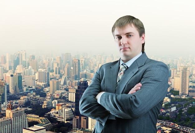Pewny siebie biznesmen stojący przed widokiem na miasto