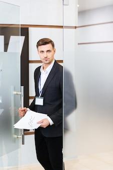 Pewny siebie biznesmen w czarnym garniturze wchodzący do biura