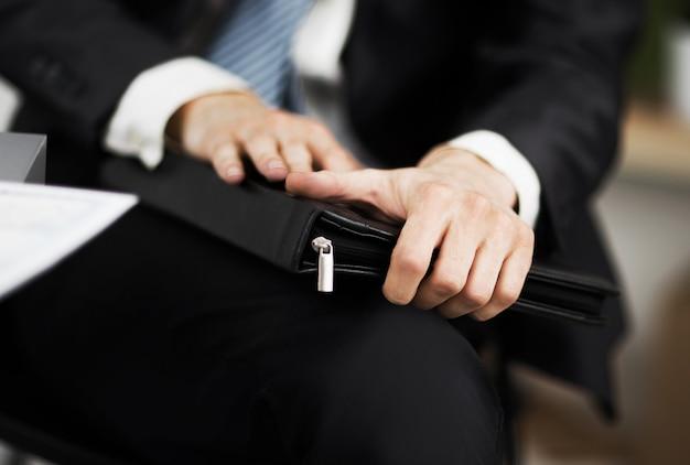 Pewny siebie biznesmen z teczką w ręku w biurze