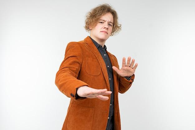 Pewny siebie blondyn w brązowej kurtce z rękami skrzyżowanymi odmawia na tle białego studia.