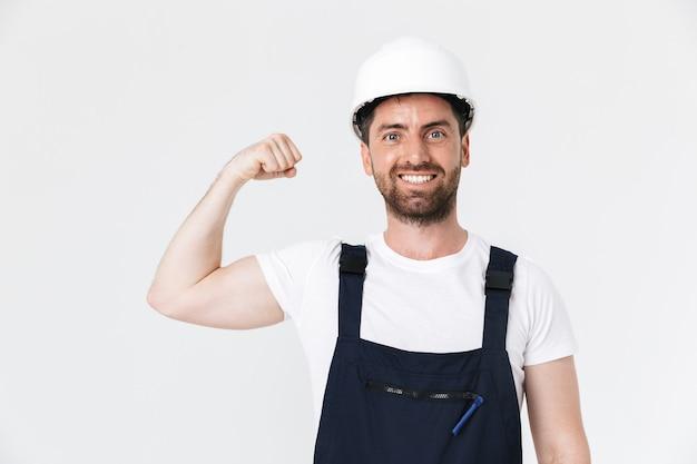 Pewny siebie, brodaty budowniczy mężczyzna w kombinezonie i kasku stojącym na białym tle nad białą ścianą, napinający mięśnie