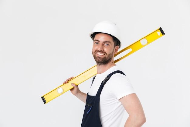 Pewny siebie, brodaty budowniczy mężczyzna w kombinezonie i kasku stojącym na białym tle nad białą ścianą, niosący poziom pomiaru
