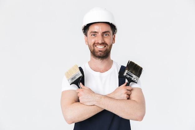 Pewny siebie, brodaty budowniczy mężczyzna w kombinezonie i kasku stojącym na białym tle nad białą ścianą, pokazując pędzle
