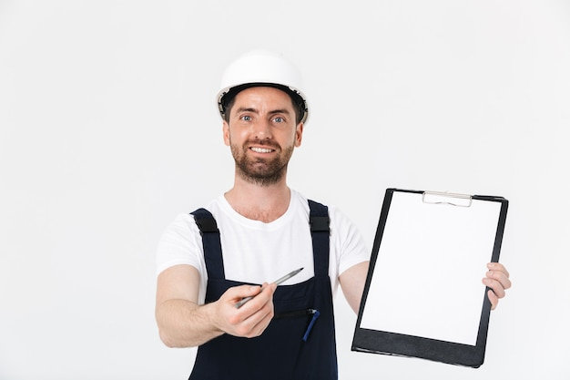 Pewny siebie, brodaty budowniczy mężczyzna w kombinezonie i kasku stojącym na białym tle nad białą ścianą, pokazując pustą tabliczkę