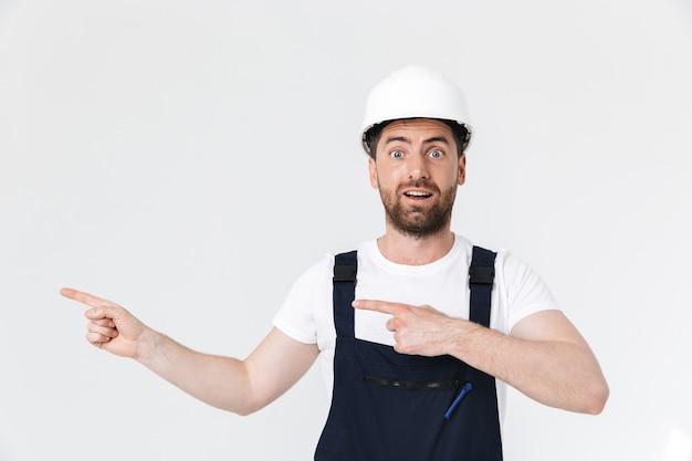 Pewny siebie, brodaty budowniczy mężczyzna w kombinezonie i kasku stojącym na białym tle nad białą ścianą, wskazując palcem na miejsce kopiowania