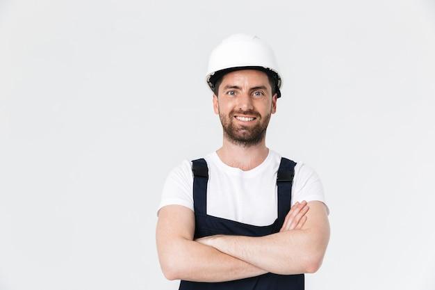 Pewny siebie, brodaty budowniczy mężczyzna w kombinezonie i kasku stojącym na białym tle nad białą ścianą, z założonymi rękami