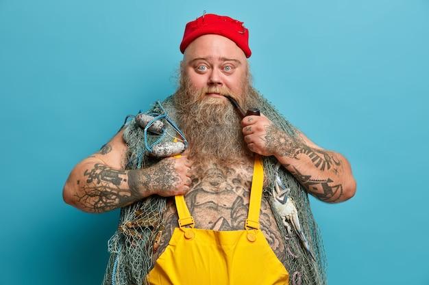 Pewny siebie brodaty marynarz patrzy poważnie w kamerę pali fajkę i pozuje z siecią rybacką ma tatuaże nosi czerwony kapelusz z haczykami na ryby lubi ulubione hobby