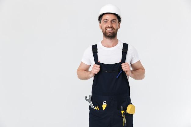 Pewny siebie, brodaty mężczyzna budowniczy w kombinezonie i kasku stojącym na białym tle nad białą ścianą