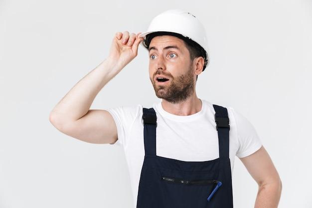 Pewny siebie, brodaty mężczyzna, ubrany w kombinezon i kask, stojący na białym tle nad białą ścianą, odwracający wzrok