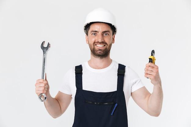 Pewny siebie, brodaty mężczyzna w kombinezonie i kasku stojącym na białym tle nad białą ścianą, pokazując klucz nastawny