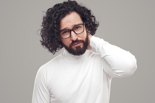 Pewny siebie brodaty mężczyzna w okularach patrzący w kamerę