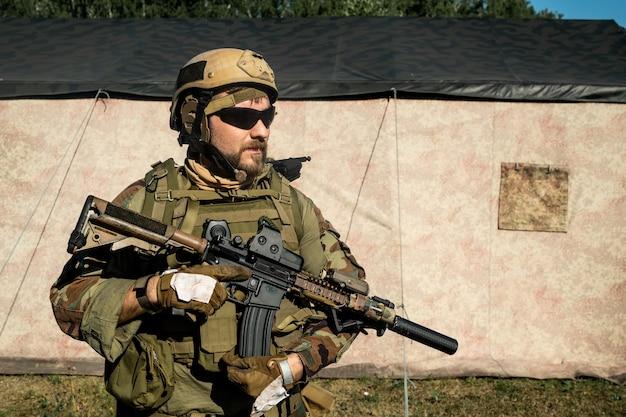 Pewny siebie brodaty żołnierz w kamuflażu i hełmie trzymający karabin i patrzący w dal