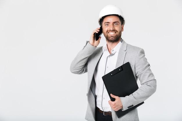 Pewny siebie budowniczy brodaty mężczyzna ubrany w garnitur i kask stojący na białym tle nad białą ścianą, rozmawiający przez telefon komórkowy