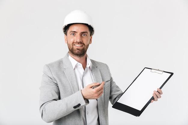 Pewny siebie budowniczy brodaty mężczyzna w garniturze i kasku stojącym na białym tle nad białą ścianą, pokazując pusty notatnik