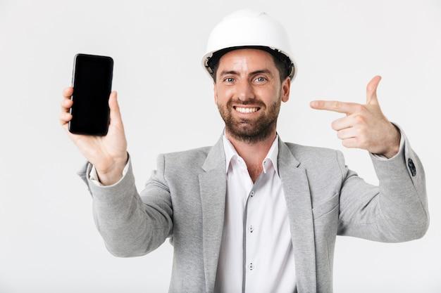 Pewny siebie budowniczy brodaty mężczyzna w garniturze i kasku stojącym na białym tle nad białą ścianą, pokazujący pusty ekran telefonu komórkowego