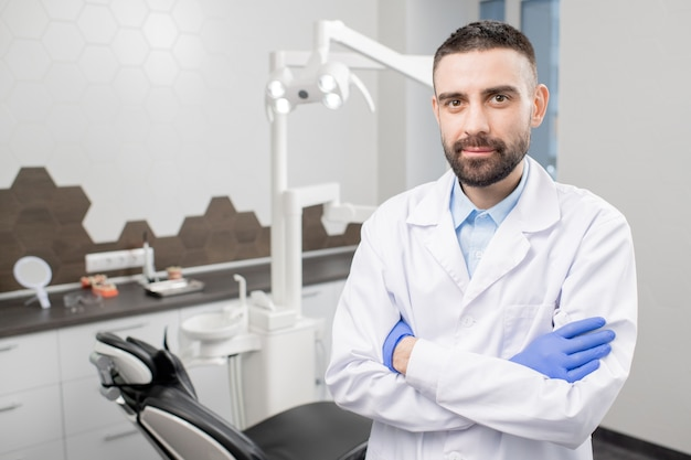 Pewny siebie dentysta z brodą skrzyżowaną na piersiach stojąc obok miejsca pracy
