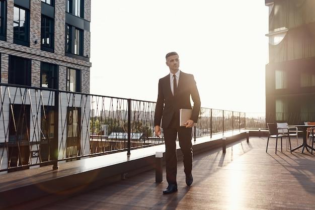 Pewny siebie dojrzały mężczyzna w pełnym garniturze niosący laptopa podczas spaceru po tarasie centrum biznesowego na świeżym powietrzu