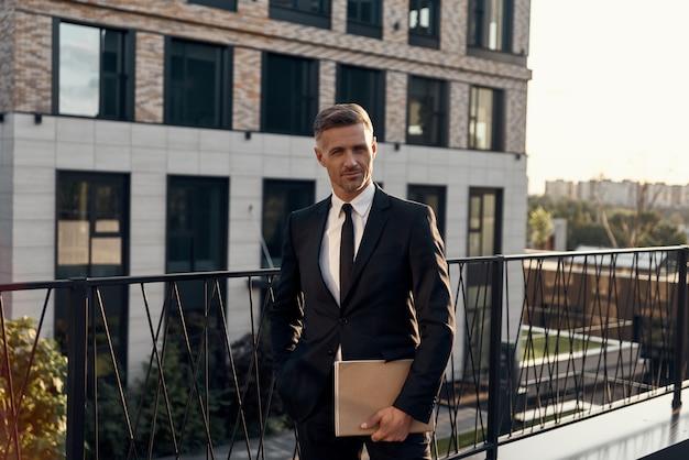Pewny siebie dojrzały mężczyzna w pełnym garniturze niosący laptopa stojąc na tarasie centrum biznesowego