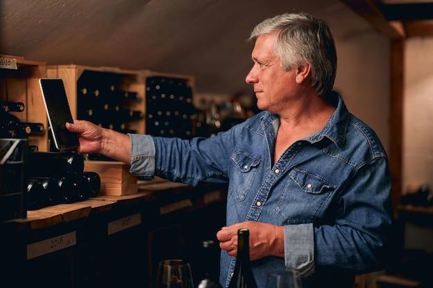 Pewny siebie dojrzały sommelier uśmiechający się i trzymający tablet przed półką z butelkami wina