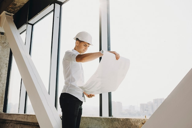 Pewny siebie dorosły architekt oglądający plan budowanego budynku przy dużym oknie.