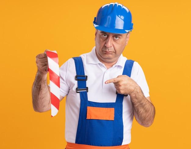 Pewny siebie dorosły budowniczy mężczyzna w mundurze trzyma i wskazuje na taśmę klejącą na białym tle na pomarańczowej ścianie