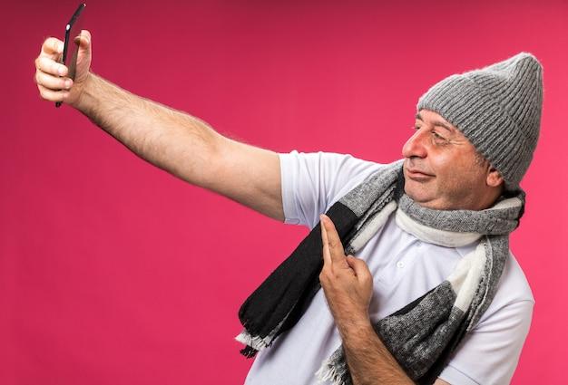 Pewny siebie dorosły chory kaukaski mężczyzna z szalikiem na szyi w czapce zimowej biorący selfie gestykulujący znak zwycięstwa odizolowany na różowej ścianie z kopią miejsca