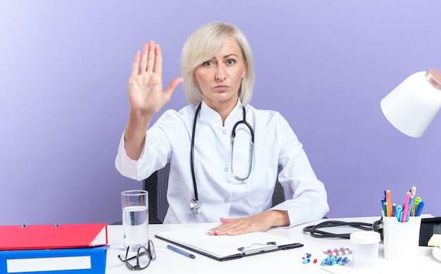 Pewny siebie dorosły lekarz w szacie medycznej ze stetoskopem siedzący przy biurku z narzędziami biurowymi gestykulujący znak stopu odizolowany na fioletowej ścianie z kopią miejsca