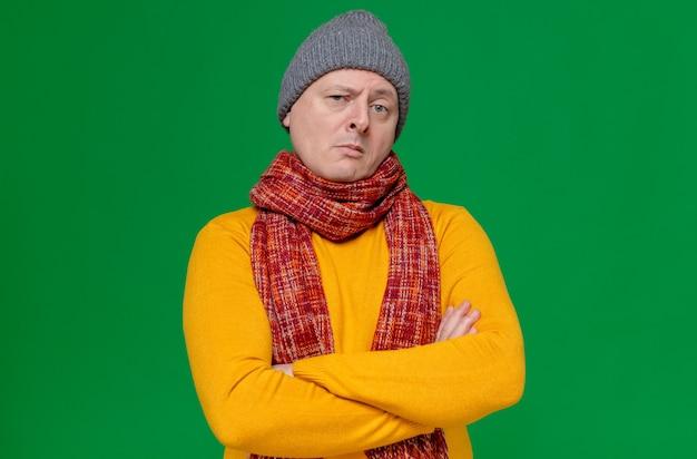 Pewny siebie dorosły mężczyzna w czapce zimowej i szaliku na szyi, stojący ze skrzyżowanymi rękami i patrzący