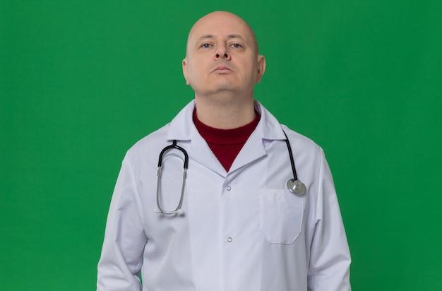Pewny siebie dorosły mężczyzna w mundurze lekarza ze stetoskopem patrzącym w górę