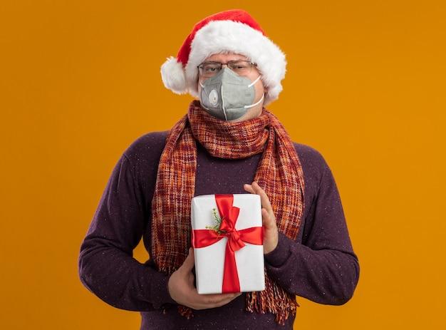 Pewny siebie dorosły mężczyzna w okularach ochronnych z maską i santa hat z szalikiem na szyi, trzymając pakiet prezentów patrząc na aparat na białym tle na pomarańczowym tle