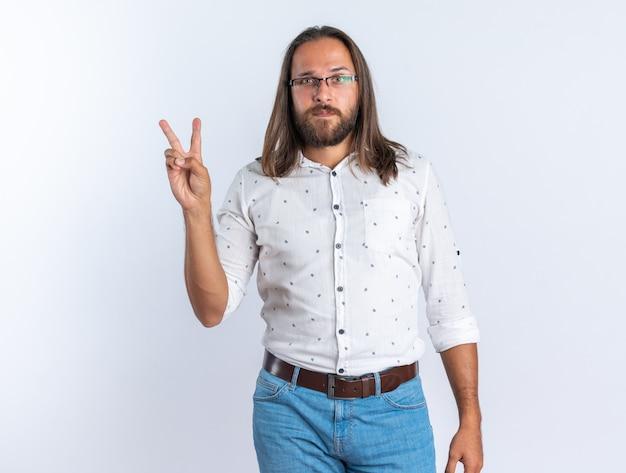 Pewny siebie dorosły przystojny mężczyzna w okularach, patrząc na kamerę robi znak pokoju na białym tle na białej ścianie