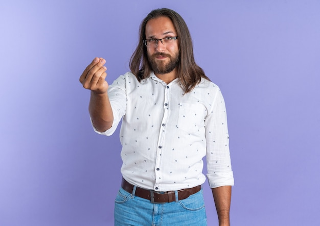 Pewny siebie dorosły przystojny mężczyzna w okularach, patrząc na kamerę, wykonując gest pieniędzy na fioletowej ścianie
