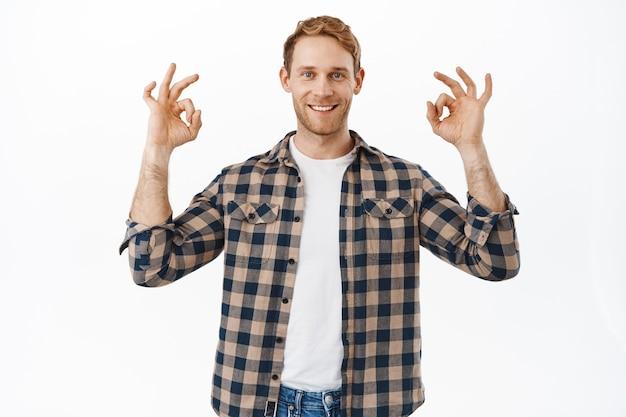 Pewny siebie dorosły rudy mężczyzna pokazujący tak ok, dobry gest i uśmiechnięty szczęśliwy, gwarantuje wszystko pod kontrolą, nie ma problemu, dobry gest, kiwa głową z aprobatą, pochwala dobrą jakość, biała ściana