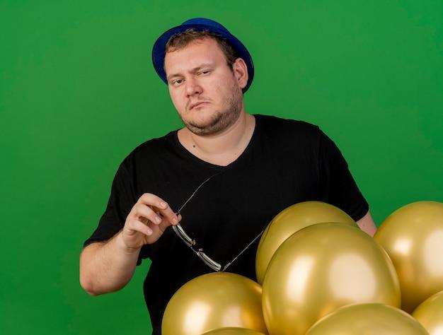 Pewny siebie dorosły słowiański mężczyzna trzyma okulary optyczne w niebieskiej imprezowej czapce stojącej z balonami z helem