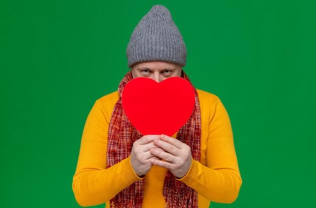 Pewny siebie dorosły słowiański mężczyzna w czapce zimowej i szaliku na szyi, trzymający kształt czerwonego serca i patrzący z przodu