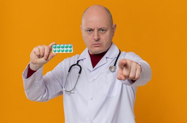 Pewny siebie dorosły słowiański mężczyzna w mundurze lekarza ze stetoskopem trzymający blister z lekiem, patrząc i wskazując z przodu