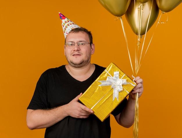 Pewny siebie dorosły słowiański mężczyzna w okularach optycznych, noszący czapkę urodzinową, trzyma balony z helem i pudełko upominkowe