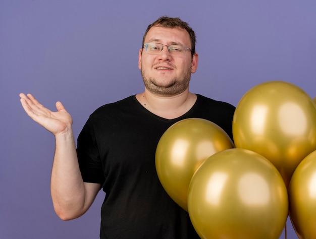 Pewny siebie dorosły słowiański mężczyzna w okularach optycznych stoi z balonami z helem i trzyma otwartą dłoń