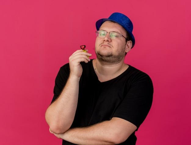 Pewny siebie dorosły słowiański mężczyzna w okularach optycznych w niebieskim kapeluszu imprezowym trzyma gwizdek na imprezę