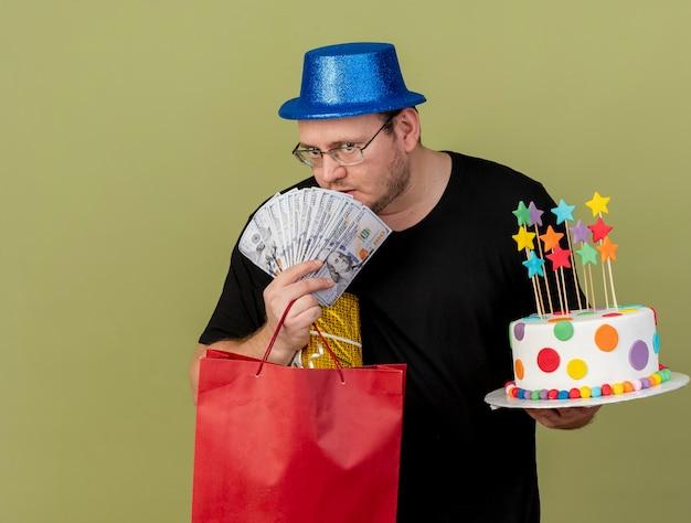 Pewny siebie dorosły słowiański mężczyzna w okularach optycznych w niebieskim kapeluszu imprezowym trzyma pudełko z pieniędzmi papierową torbę na zakupy i tort urodzinowy