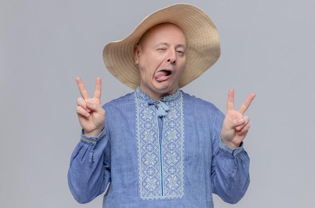 Pewny siebie dorosły słowiański mężczyzna w słomkowym kapeluszu i niebieskiej koszuli mruga okiem i gestykuluje znak zwycięstwa