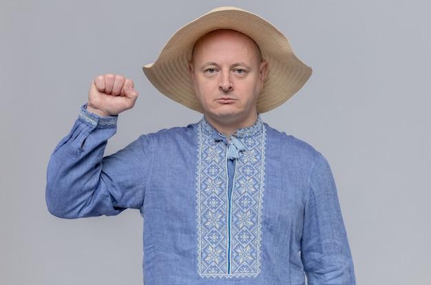 Pewny siebie dorosły słowiański mężczyzna w słomkowym kapeluszu i niebieskiej koszuli trzymającej pięść w górze