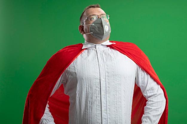 Pewny siebie dorosły słowiański superbohater w czerwonej pelerynie w okularach i masce ochronnej trzymający ręce w talii patrząc w górę odizolowany na zielonej ścianie